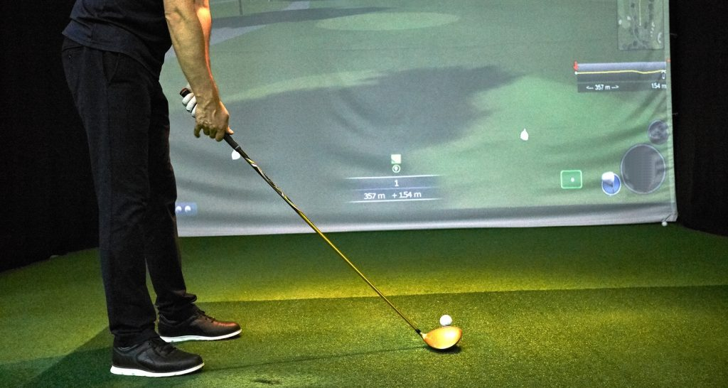 Golfer practices on a golf simulator