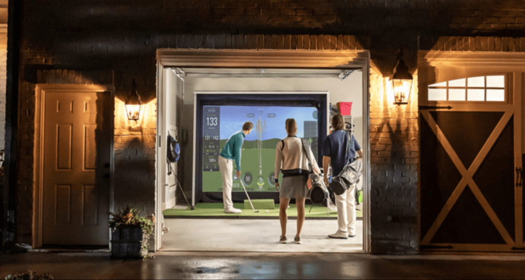 Skytrack's launch monitor being used by a player, inside a garage, along with 2 more players watching.
