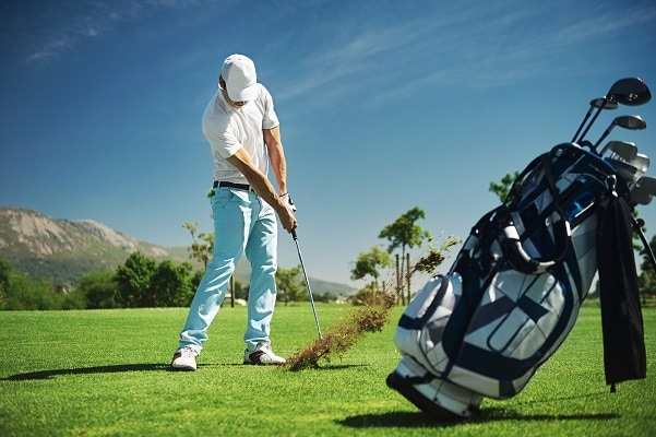 golfer hits ball on golf course